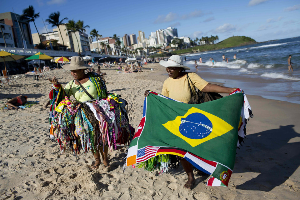 Photo - Street vendors sell swim wear and a Brazilian flags on the beach in Salvador, Brazil, Monday, June 30, 2014. Salvador is on of the host cities of the FIFA 2014 Soccer World Cup. (AP Photo/Rodrigo Abd)
