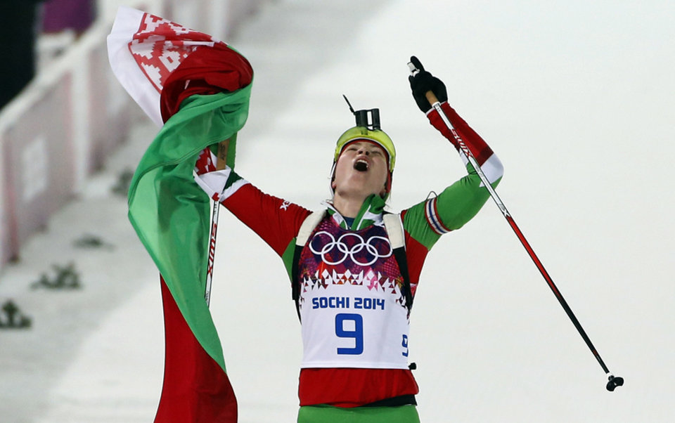 Photo - Belarus' Darya Domracheva celebrates after winning the gold medal in the women's biathlon 10k pursuit, at the 2014 Winter Olympics, Tuesday, Feb. 11, 2014, in Krasnaya Polyana, Russia. (AP Photo/Felipe Dana)