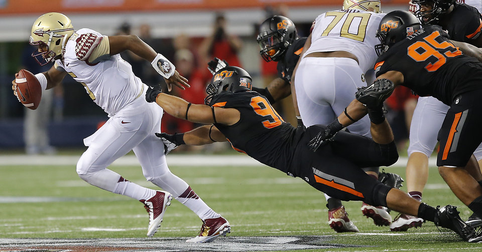 Photo - Florida State's Jameis Winston (5) breaks away from Oklahoma State's Ofa Hautau (98) during the college football game between Oklahoma State University (OSU) and Florida State University (FSU) at the AdvoCare Cowboys Classic at AT&T Stadium in Arlington, Texas on Saturday, Aug. 30, 2014. Photo by Chris Landsberger, The Oklahoman