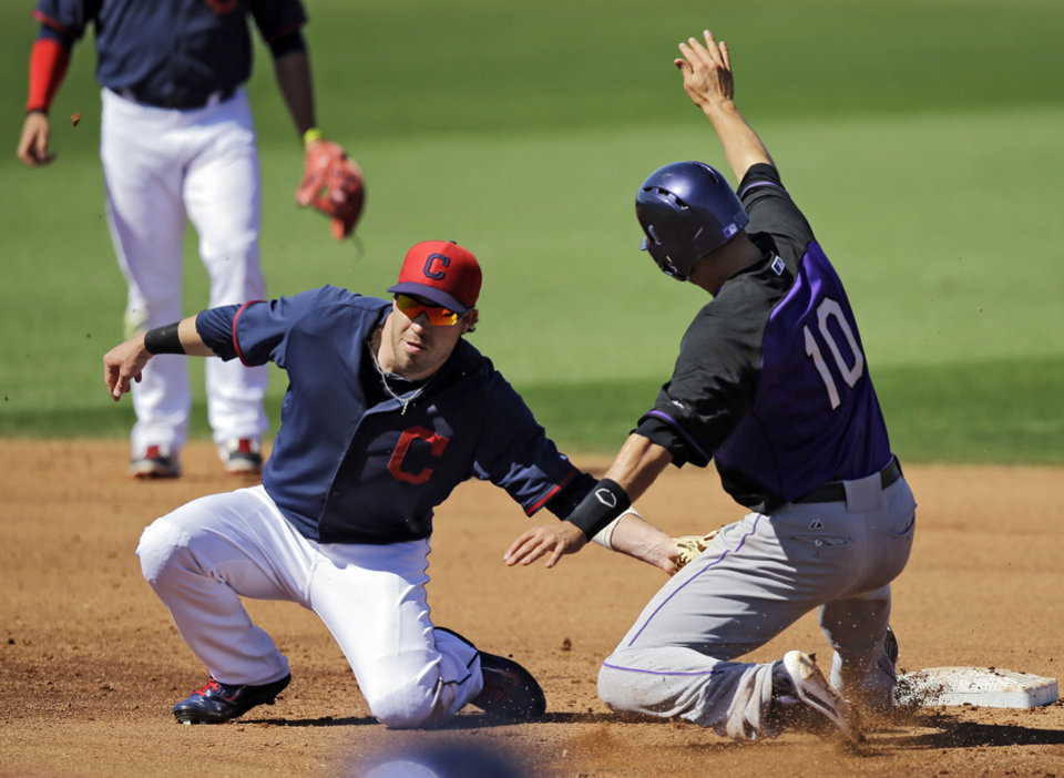 Photo - Cleveland Indians second baseman Jason Kipnis tags out Colorado Rockies' Paul Janish (10) attempting to steal second base in the fifth inning of a spring exhibition baseball game, Saturday, March 22, 2014, in Goodyear, Ariz. (AP Photo/Mark Duncan)