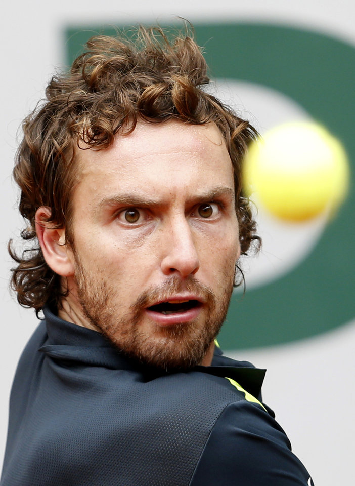 Photo - Latvia's Ernests Gulbis eyes the ball as he plays Argentina's Facundo Bagnis during their second round match of  the French Open tennis tournament at the Roland Garros stadium, in Paris, France, Wednesday, May 28, 2014. (AP Photo/Darko Vojinovic)