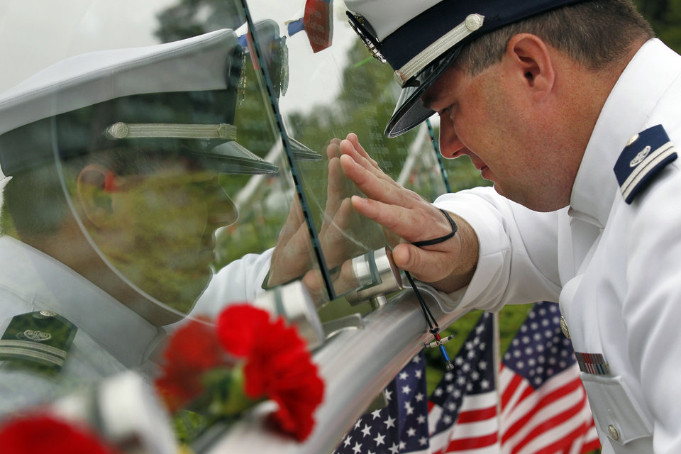 A U.S. Coast Guard Lieutenant who asked that his name not be used, kneels near his father's name after a remembrance ceremony at the Garden of Reflection Sunday, Sept. 11, 2011 in Yardley, Pa. The memorial honors nine people from Lower Makefield Township, where the memorial is located, eighteen people from Bucks County, and all 58 people from Pennsylvania that lost their lives in the attacks Sept. 11, 2001. (AP Photo/Alex Brandon)