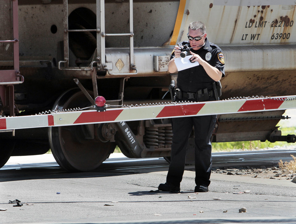 Photo - A BNSF officer investigates the scene of a pedestrian/train fatality at Boyd west of Classen on Saturday, Sept. 1, 2012 in Norman, Okla.  Photo by Steve Sisney, The Oklahoman