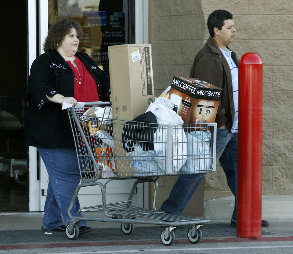 Photo - Jonni and Frank Garcia find some good buys at the Wal-Mart at Pennsylvania and Memorial in Oklahoma City, OK, on Black Friday, Nov. 27, 2009. By Paul Hellstern, The Oklahoman