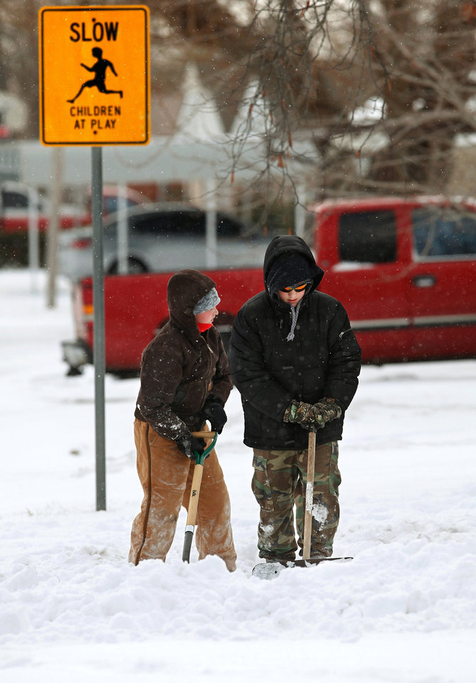 Photo - Buddies James Allison, 11, left, and Jacob Freitas, 13, and another friend  grabbed shovels and set out Wednesday morning asking neighbors in their Del City neighborhood  to hire the trio to clear snow from their sidewalks and driveways. The boys are pictured clearing a driveway on a street called Wofford.  The boys said they teamed last summer to operate a lemonade stand to earn extra spending cash.  A second winter storm in a week dumped about 6 inches of snow in the Oklahoma City area Tuesday morning, Feb. 9, 2011.   Photo by Jim Beckel, The Oklahoman