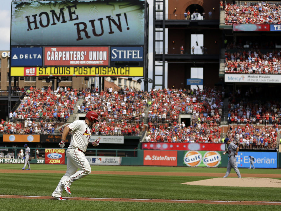 Photo - St. Louis Cardinals' Matt Adams, left, rounds the bases after hitting a two-run home run off Los Angeles Dodgers starting pitcher Zack Greinke, right, during the first inning of a baseball game Saturday, July 19, 2014, in St. Louis. (AP Photo/Jeff Roberson)