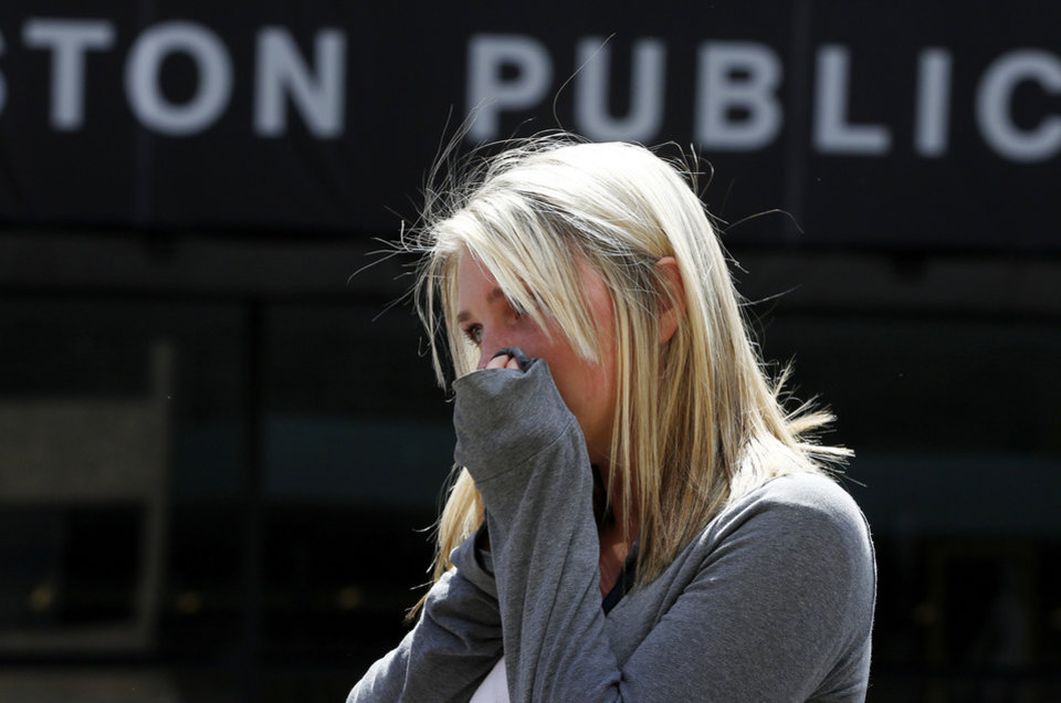 Photo - An unidentified woman visits the site where the first bomb detonated on April 15 near the finish line of the Boston Marathon on Boylston Street in Boston, Wednesday, April 24, 2013. Traffic was allowed to flow all the way down Boylston Street on Wednesday morning for the first time since two explosions. (AP Photo/Michael Dwyer)