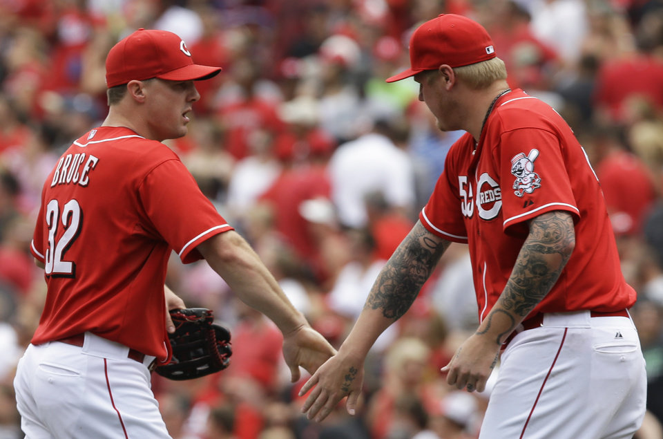 Photo - Cincinnati Reds' Jay Bruce, left, is congratulated by starting pitcher Mat Latos, right,  after they defeated the Milwaukee Brewers 4-2 in a baseball game, Sunday, July 6, 2014, in Cincinnati. Bruce hit a two-run home run and Latos was the winning pitcher. (AP Photo/Al Behrman)