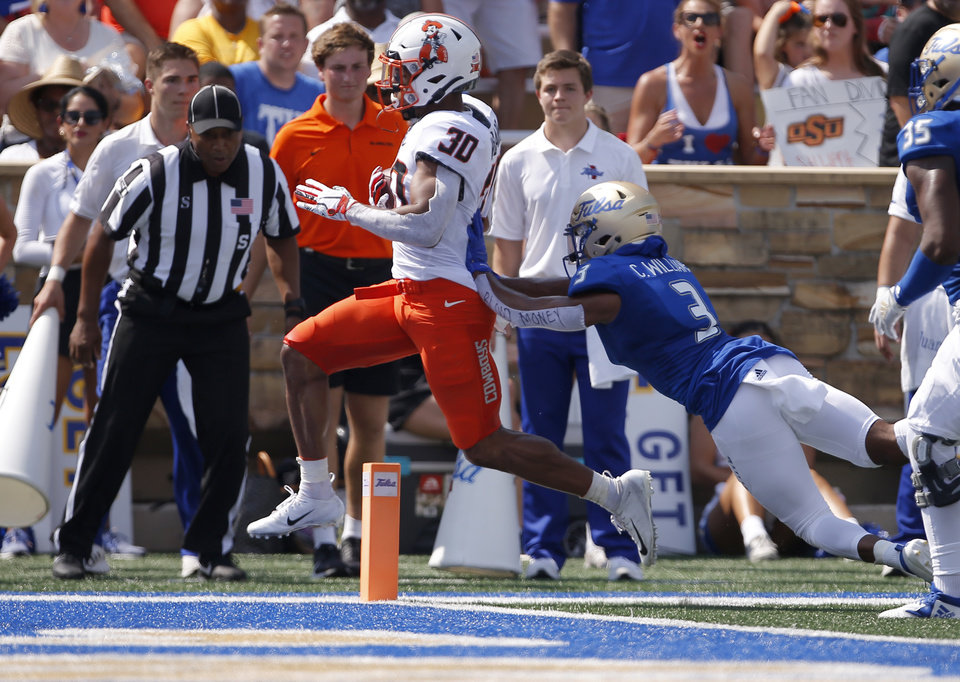 Photo - Oklahoma State's Chuba Hubbard (30) scores a touchdown as Tulsa's Cristian Williams (3) defends in the first quarter during a college football game between the Oklahoma State University Cowboys (OSU) and the University of Tulsa Golden Hurricane (TU) at H.A. Chapman Stadium in Tulsa, Okla., Saturday, Sept. 14, 2019. [Sarah Phipps/The Oklahoman]