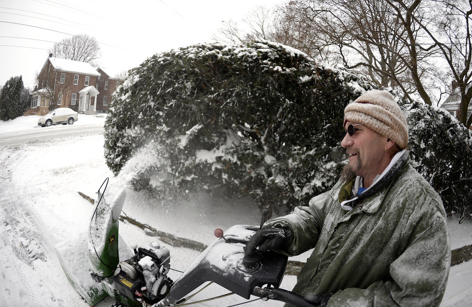 Photo - In this photo taken with a fisheye lens, John Keener of Lebanon uses a snow blower to clear part of a street in Lebanon, Pa. on Tuesday, Jan. 21, 2014. The National Weather Service predicts the storm could drop 8 to 12 inches of snow followed by bitterly cold temperatures. (AP Photo/Lebanon Daily News, Jeremy Long)  THE PATRIOT-NEWS OUT