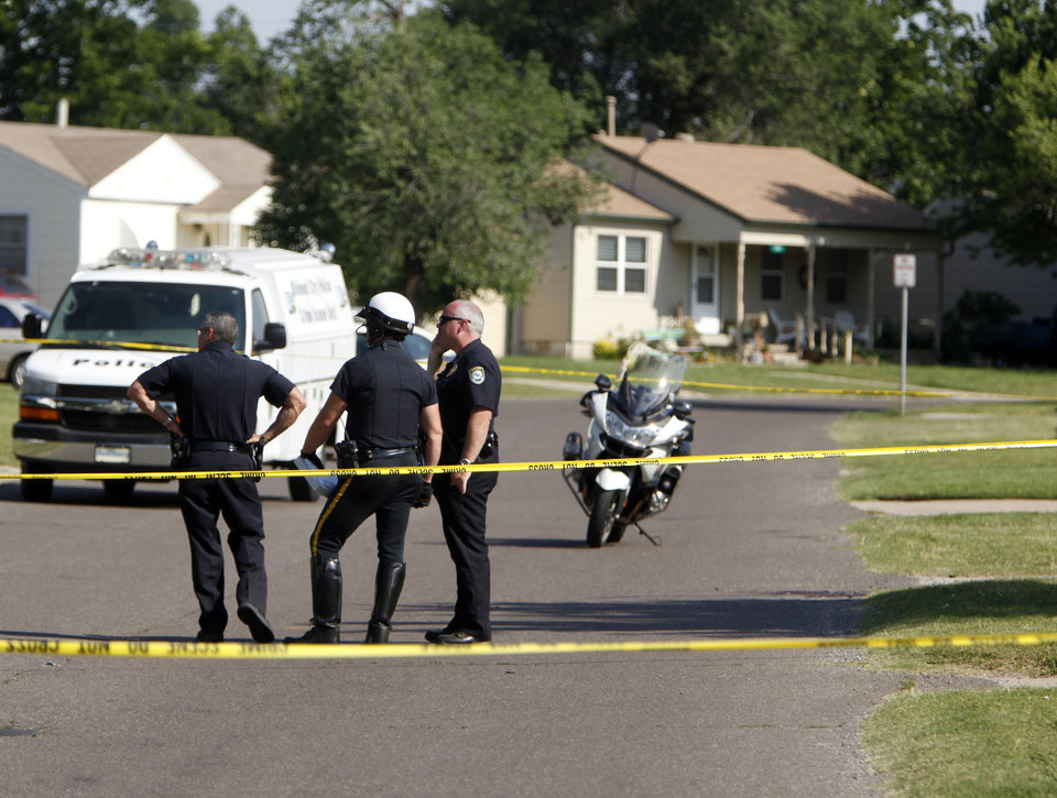 Photo - Police investigate a shooting Friday in a neighborhood near Midwest City High School. Photos by Sarah Phipps, The Oklahoman