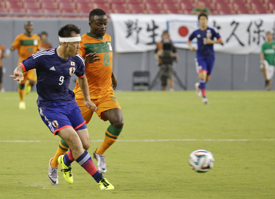 Photo - Japan's Shinji Okazaki (9) clears the ball away from Zambia's Isaac Chansa (8) during the first half of an international friendly soccer match in Tampa, Fla., Friday, June 6, 2014. (AP Photo/John Raoux)