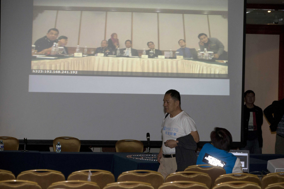 Photo - Wen Wanchang, whose son was on board the missing Malaysia Airlines 370, walks out to protest the difficulties of communicating with Malaysian officials through video conferencing in Beijing, China, Wednesday, April 16, 2014. A robotic submarine looking for the lost Malaysian jet continued its second seabed search on Wednesday as up to 14 planes were to take to the skies for some of the final sweeps of the Indian Ocean for floating debris from the ill-fated airliner. (AP Photo/Ng Han Guan)