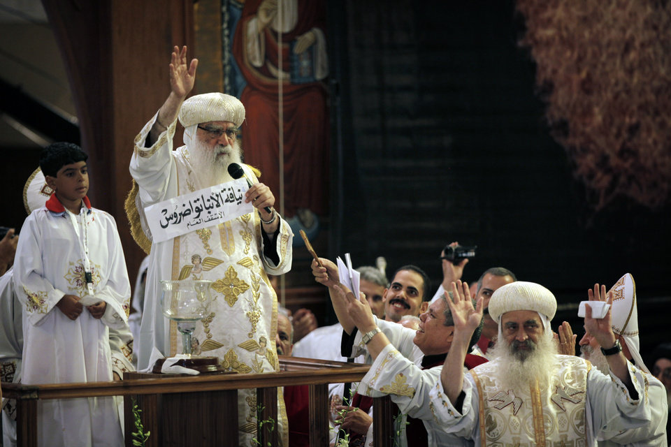 Photo -   Acting Coptic Pope Pachomios, center, displays the name of 60-year-old Bishop Tawadros, soon to be Pope Tawadros II, during the papal election ceremony at the Coptic Cathedral in Cairo, Egypt, Sunday, Nov. 4, 2012. Egypt's ancient Coptic Christian church chose a new pope in an elaborate Sunday ceremony meant to invoke the will of God, in which a blindfolded boy drew the name of the next patriarch from a crystal chalice. (AP Photo/Nasser Nasser)