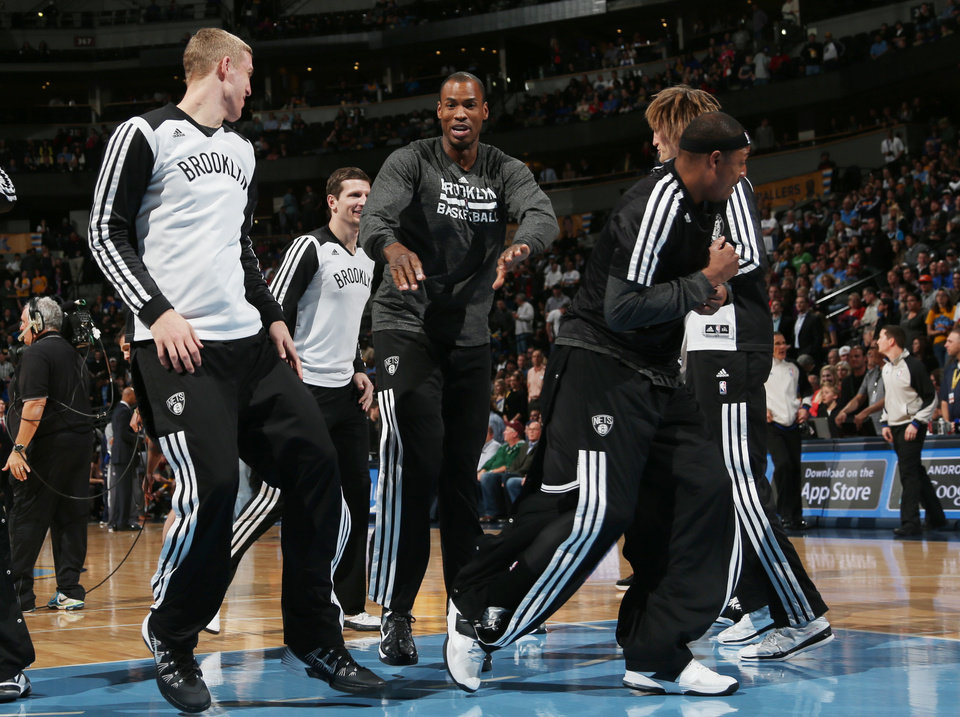 Photo - Brooklyn Nets center Jason Collins, center, jokes with teammates during player introductions before the Nets faced the Denver Nuggets in an NBA basketball game in Denver on Thursday, Feb. 27, 2014. (AP Photo/David Zalubowski)