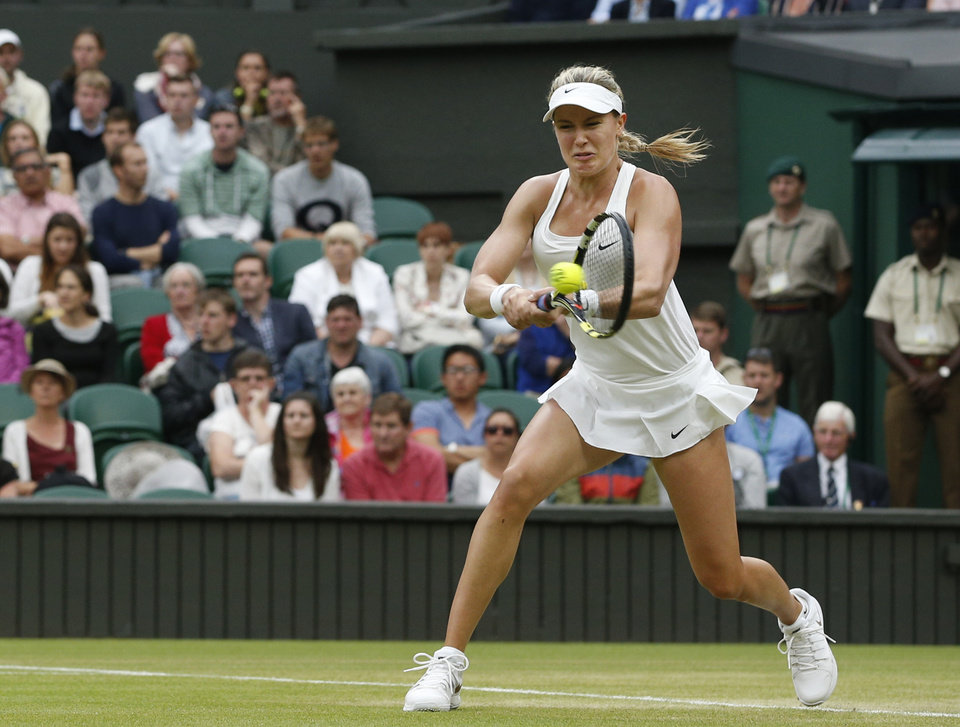 Photo - Eugenie Bouchard of Canada plays a return to Alize Cornet of France during their women's singles match at the All England Lawn Tennis Championships in Wimbledon, London, Monday, June 30, 2014. (AP Photo/Pavel Golovkin)