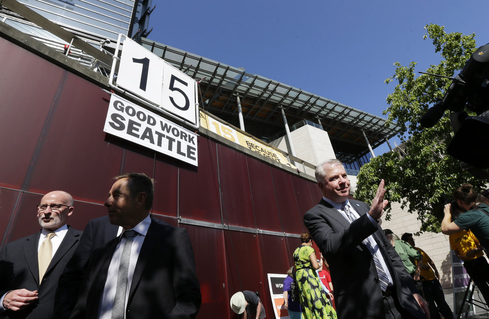 Photo - Seattle Mayor Ed Murray, right, waves to the crowd after a sign that reads