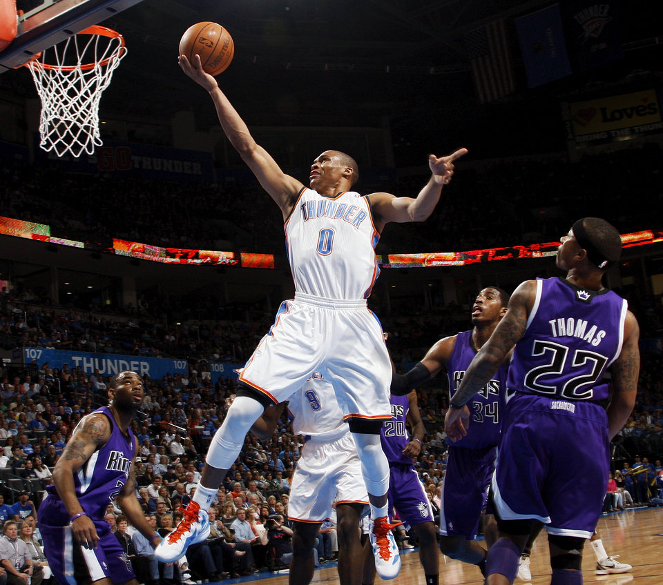 Oklahoma City's Russell Westbrook (0) flies to the hoop past Sacramento's Marcus Thornton (23), Donte Greene (20), Jason Thompson (34) and Isaiah Thomas (22)  during the NBA basketball game between the Oklahoma City Thunder and the Sacramento Kings at Chesapeake Energy Arena in Oklahoma City, Friday, April 13, 2012. Photo by Nate Billings, The Oklahoman