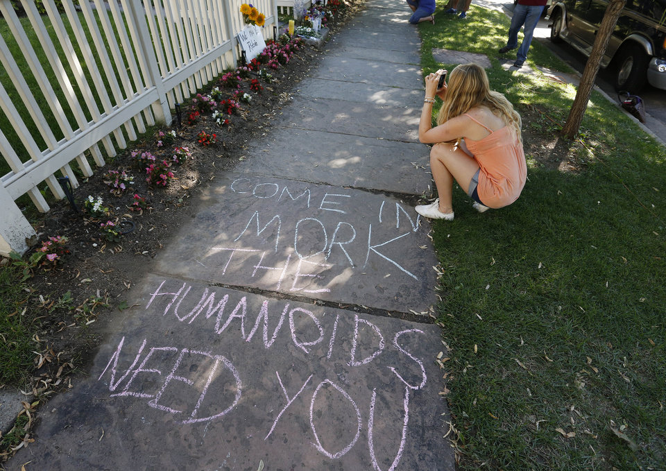 Photo - A woman takes a picture next to a sign written in chalk at a makeshift memorial outside the home where the 80s TV series Mork & Mindy, starring the late Robin Williams, was set, in Boulder, Colo., Tuesday Aug. 12, 2014. Williams, the Academy Award winner and comic supernova whose explosions of pop culture riffs and impressions dazzled audiences for decades and made him a gleamy-eyed laureate for the Information Age, died Monday, Aug. 11, in an apparent suicide. He was 63. (AP Photo/Brennan Linsley)