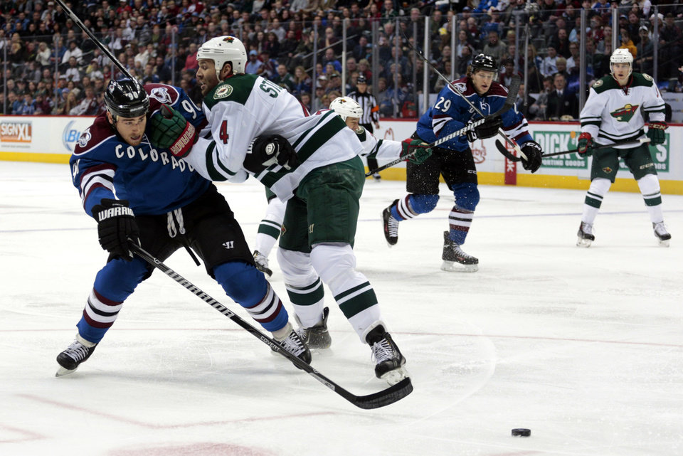 Minnesota Wild defenseman Clayton Stoner (4) pushes Colorado Avalanche center Ryan O'Reilly away from the puck during the first period of an NHL hockey game in Denver on Saturday, Dec. 14, 2013. (AP Photo/Joe Mahoney)