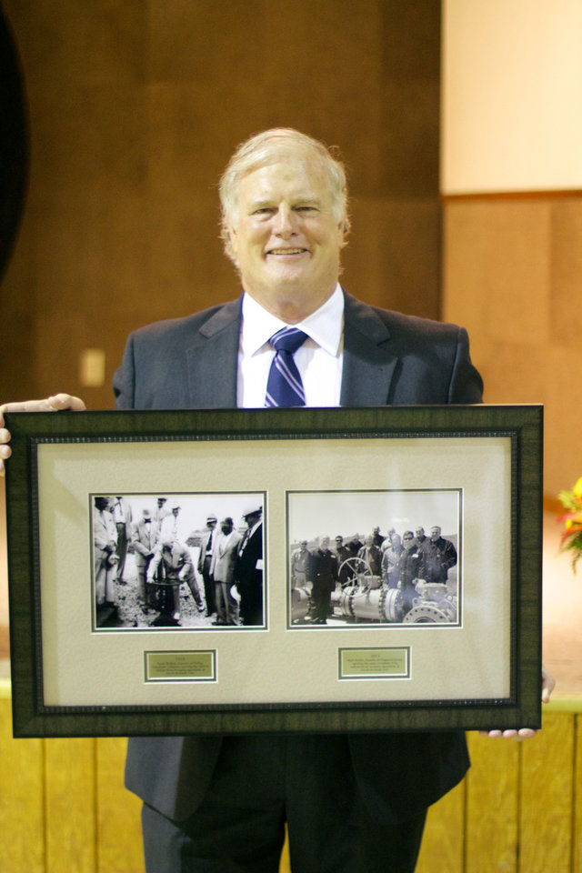 Chaparral Energy CEO Mark Fischer holds photos of Phillips Petroleum executives starting secondary waterflooding operations in Osage County in 1950 and Chaparral executives starting carbon dioxide tertiary operations on teh same field earlier this month. photo by Adam Wilmoth