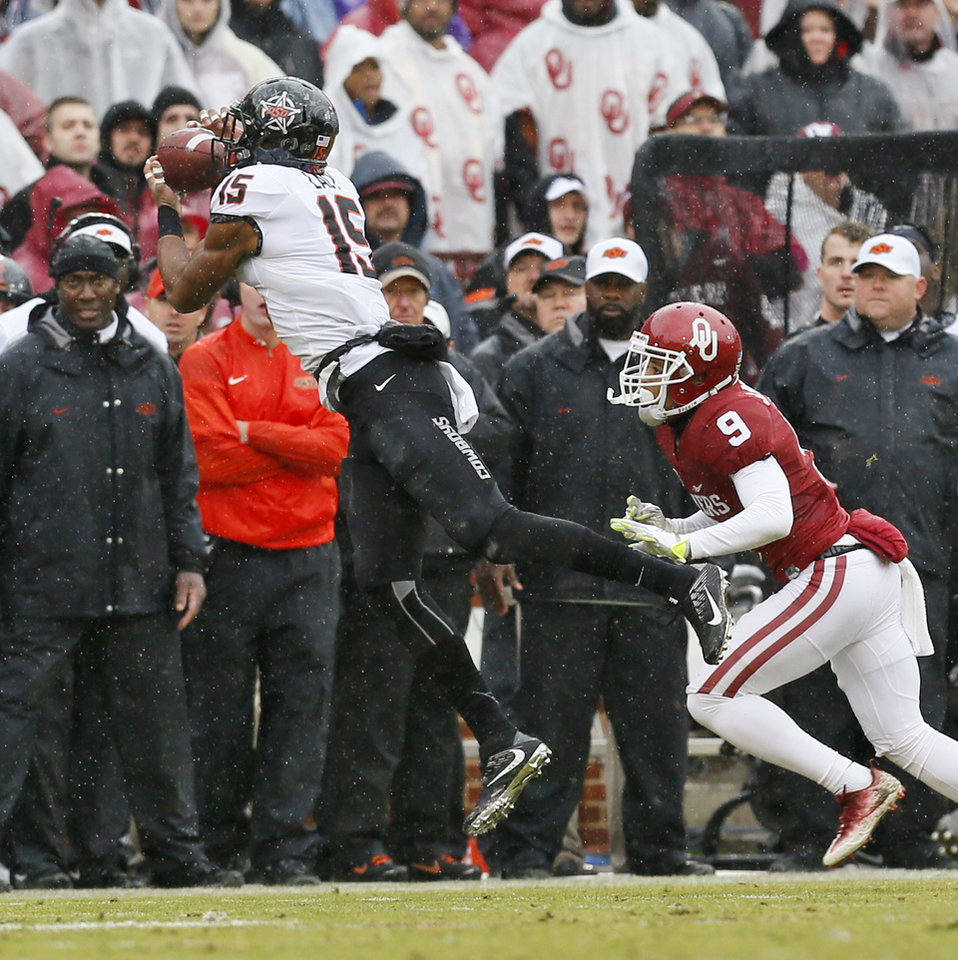 Photo - Oklahoma State's Chris Lacy (15) makes a catch in front of Oklahoma's Jordan Parker (9) during the Bedlam college football game between the Oklahoma Sooners (OU) and the Oklahoma State Cowboys (OSU) at Gaylord Family - Oklahoma Memorial Stadium in Norman, Okla., Saturday, Dec. 3, 2016. Photo by Nate Billings, The Oklahoman