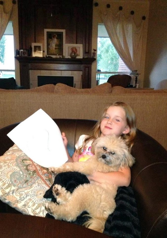 Photo - This Feb. 2014 photo provided by Dr. Danel Grimmett, shows Coral Grimmett, 5, with her dog Harry at their home in Edmund, Okla. For millions of dogs across the country, summer is gone and so are their best buddies. Most dogs object for a while but eventually adjust to the new hours.  But millions of others will feel abandoned, panicky, sad and unable to cope as they look for ways to lash out.(AP Photo/Danel Grimmett)