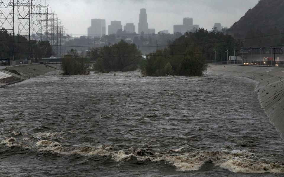 Photo - With the Los Angeles skyline in the background, the Los Angeles River flows Friday, Feb. 28, 2014. Two men and their dogs were rescued earlier from the swift waters of the LosAngelesRiver. A few miles downriver, another man was pulled out and carried to safety. Even with rainfall totals exceeding six inches in some places Friday, the powerful Pacific storm did not put a major dent in a drought that is among the worst in recent California history. (AP Photo/Damian Dovarganes)