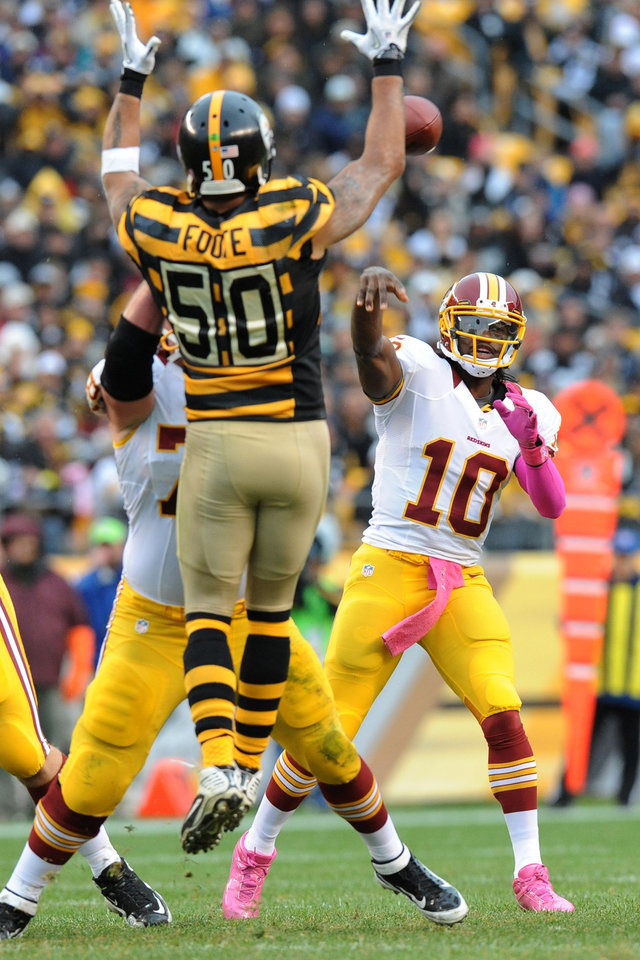 Photo -   Washington Redskins quarterback Robert Griffin III (10) tries to pass over leaping Pittsburgh Steelers inside linebacker Larry Foote (50) in the second quarter during an NFL football game on Sunday, Oct. 28, 2012, in Pittsburgh. (AP Photo/Don Wright)