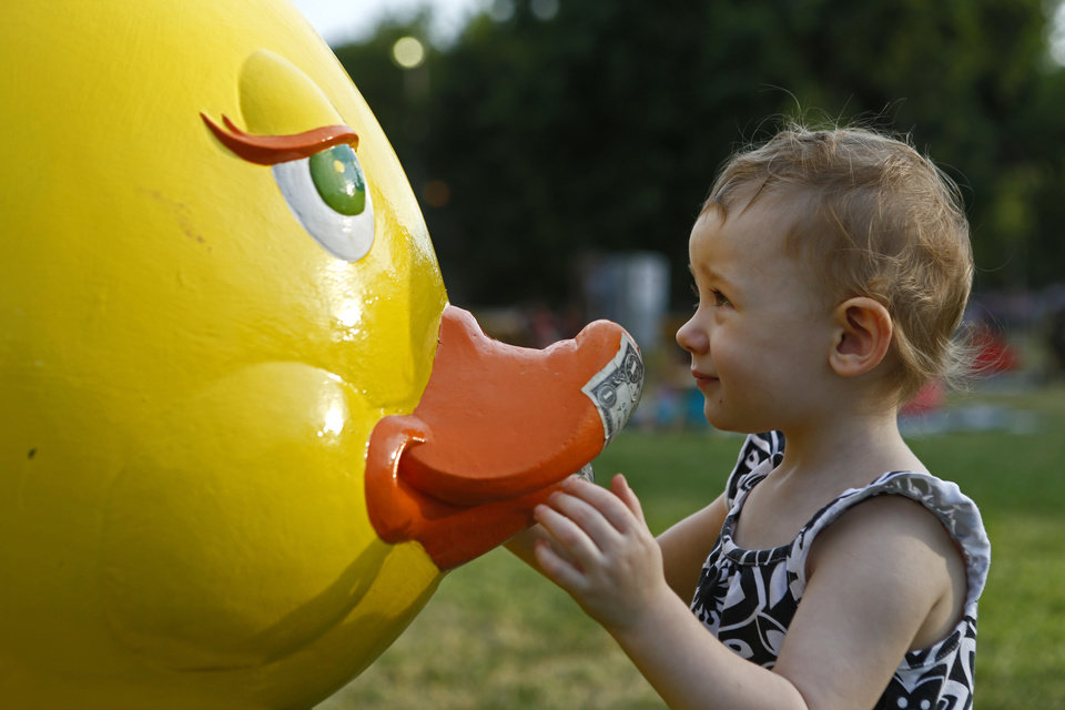 Photo - Sophia Bailey, 1, gets a close look at a duck sculpture during the Midsummer Nights' Fair. The duck is used to raise money for the children's arts programming at the Firehouse Art Center.