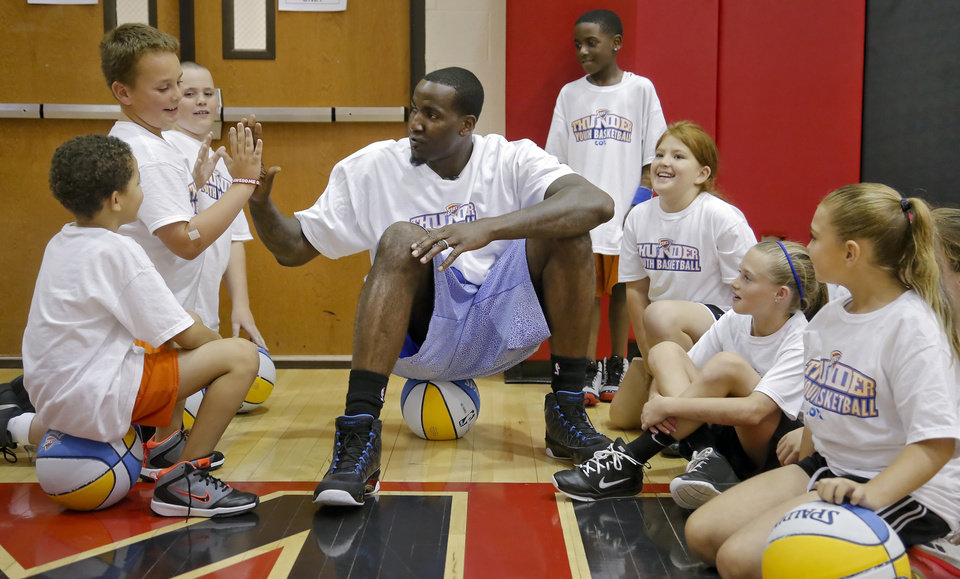 Oklahoma City Thunder's Kendrick Perkins gives out high fives to participants in the Oklahoma City Thunder basketball camp at Mid-America Christian University on Wednesday, June 19, 2013 in Oklahoma City, Okla.   Photo by Chris Landsberger, The Oklahoman