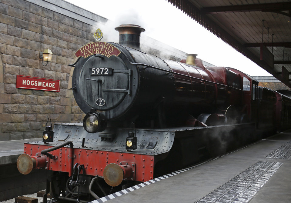 Photo - The Hogwarts Express arrives at Hogsmeade station during a preview of Diagon Alley at the Wizarding World of Harry Potter at Universal Orlando, Thursday, June 19, 2014, in Orlando, Fla. (AP Photo/John Raoux)