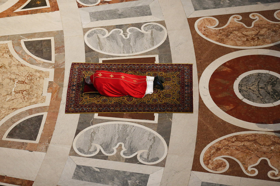Photo - Pope Francis lays prostrate on the floor in prayer before presiding over a Good Friday Passion service, in St. Peter's Basilica, at the Vatican, Friday, April  18, 2014. (AP Photo/Stefano Rellandini, Pool)