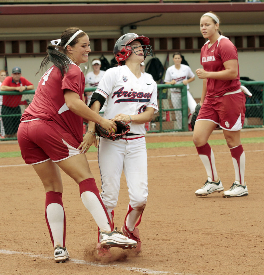 Photo - First baseman Lauren Chamberlain tags Karissa Buchanan for the final out as the University of Oklahoma Sooner Softball team sweeps Arizona in two games during the NCAA Softball Norman Super Regional at Marita Hines field on Saturday, May 26, 2012, in Norman, Okla.  Pitcher Keilani Ricketts is at right.  Photo by Steve Sisney, The Oklahoman