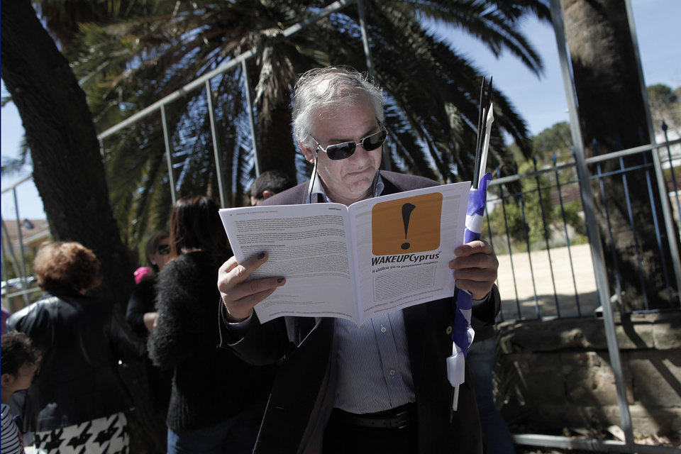 """Photo - A Cypriot man reads a leaflet handed out by protesters at the end of a parade for Greek Independence Day celebrations in capital Nicosia, Cyprus, Monday, March 25, 2013. Cyprus secured what its politicians described as a """"painful"""" solution to avert imminent bankruptcy, agreeing early Monday to slash its oversize banking sector and make large account holders take losses to help pay to secure a last-minute euro10 billion (US$13 billion) bailout. (AP Photo/Petros Giannakouris)"""