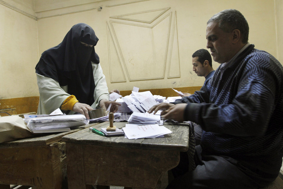 Egyptian referendum officials count votes at a polling station in Cairo, Egypt, late Saturday, Dec. 15, 2012. Egyptians took their quarrel over a draft constitution to polling stations Saturday after weeks of violent turmoil between the newly empowered Islamists and the mostly liberal opposition over the future identity of the nation.  (AP Photo/Amr Nabil)