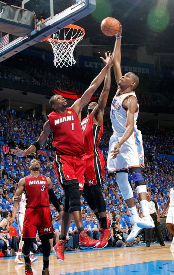Oklahoma City\'s Kevin Durant (35) goes to the basket beside Miami\'s Chris Bosh (1) and Miami\'s Udonis Haslem (40) during Game 1 of the NBA Finals between the Oklahoma City Thunder and the Miami Heat at Chesapeake Energy Arena in Oklahoma City, Tuesday, June 12, 2012. Photo by Chris Landsberger, The Oklahoman