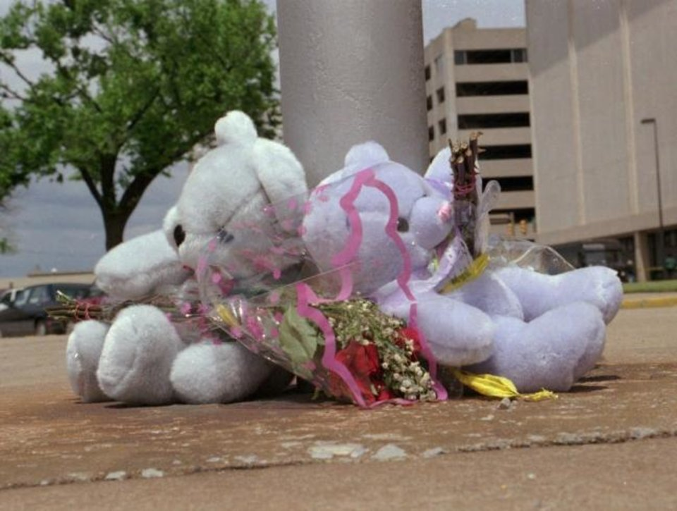 Photo -  Teddy bears and flowers were left at the flagpole in front of the city municipal building in the aftermath of the 1995 Oklahoma City bombing. [The Oklahoman Archives]