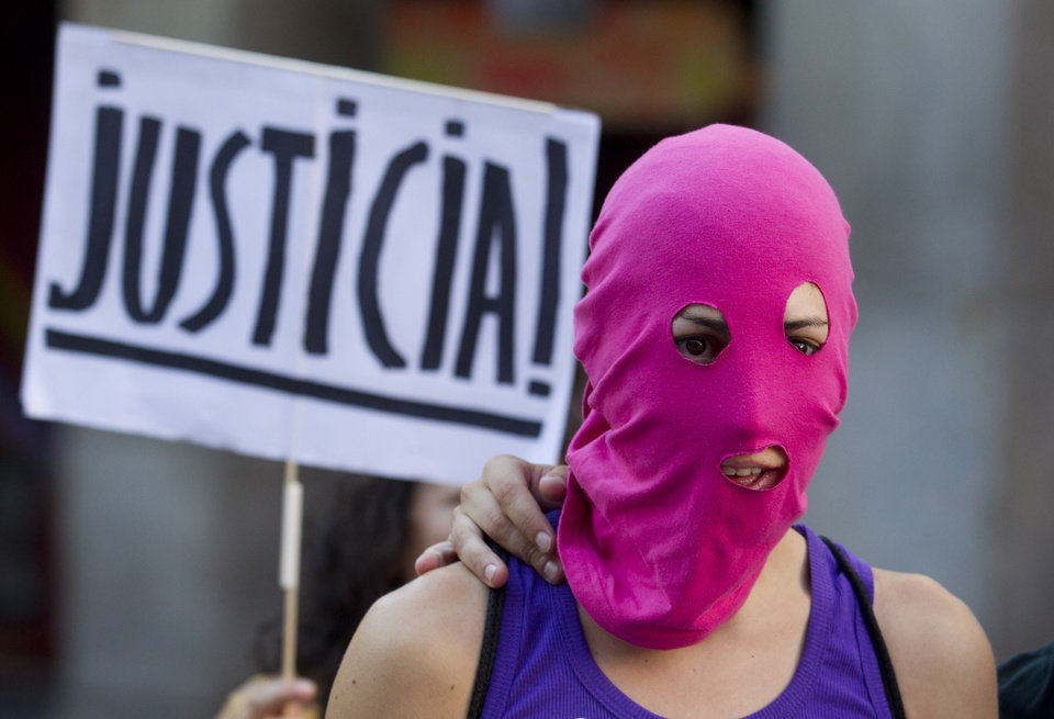Photo -   A masked demonstrator stands in front of a placard reading: 'Justice' in support of the Russian punk group Pussy Riot during a protest outside Spain's Foreign Office in Madrid Thursday Aug. 16, 2012. Three members of Pussy Riot were jailed in March and charged with hooliganism motivated by religious hatred after their punk performance against President Putin in Moscow's main cathedral. They are awaiting the verdict on Friday, Aug. 17, 2012 (AP Photo/Paul White)