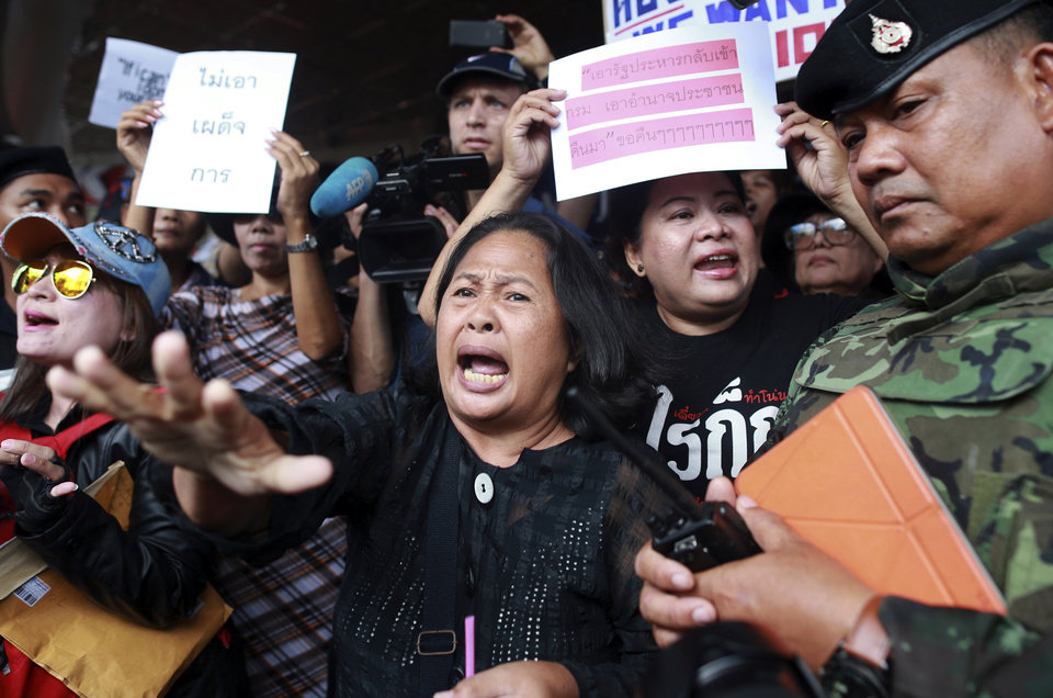 Photo - A Thai soldier, right, tries to disperse the protesters against the coup outside a shopping complex in Bangkok, Thailand Saturday, May 24, 2014. Thailand's coup leaders said Saturday they will keep former Prime Minister Yingluck Shinawatra, Cabinet members and anti-government protest leaders detained for up to a week to give them