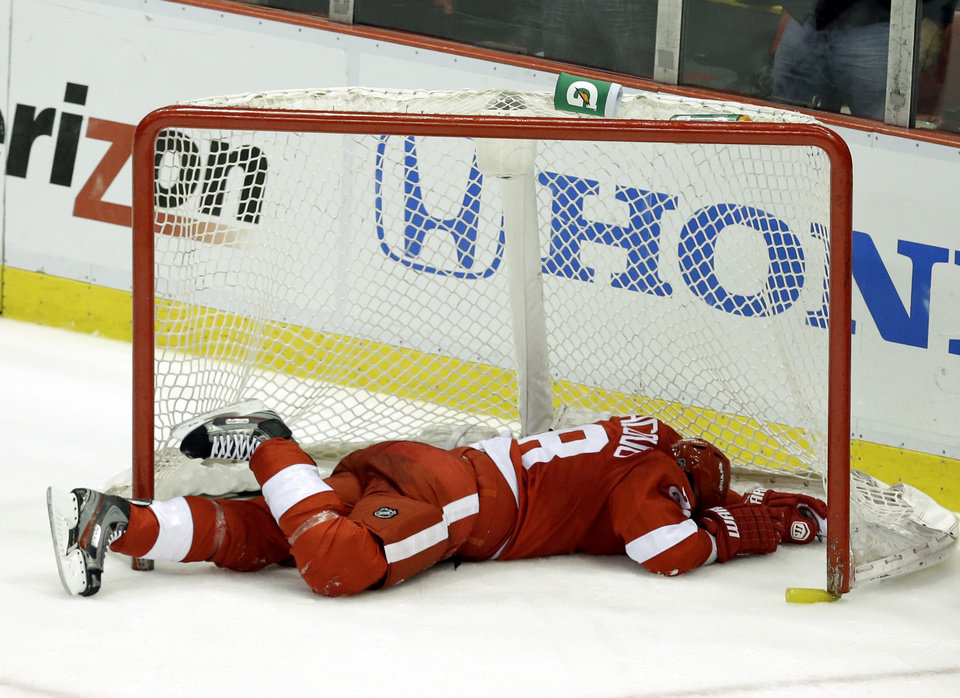 Photo - Detroit Red Wings defenseman Carlo Colaiacovo lies in the net after coming off its posts against the Chicago Blackhawks during the third period in Game 4 of the Western Conference semifinals in the NHL hockey Stanley Cup playoffs in Detroit, Thursday, May 23, 2013. (AP Photo/Paul Sancya)