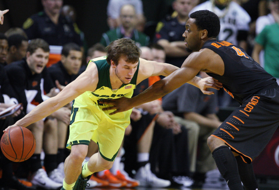 Photo - Baylor guard Brady Heslip (5) is pressured by Oklahoma State forward Brian Williams (4), right, in the first half of an NCAA college basketball game, Monday, Feb. 17, 2014, in Waco, Texas. (AP Photo/Waco Tribune Herald, Rod Aydelotte)