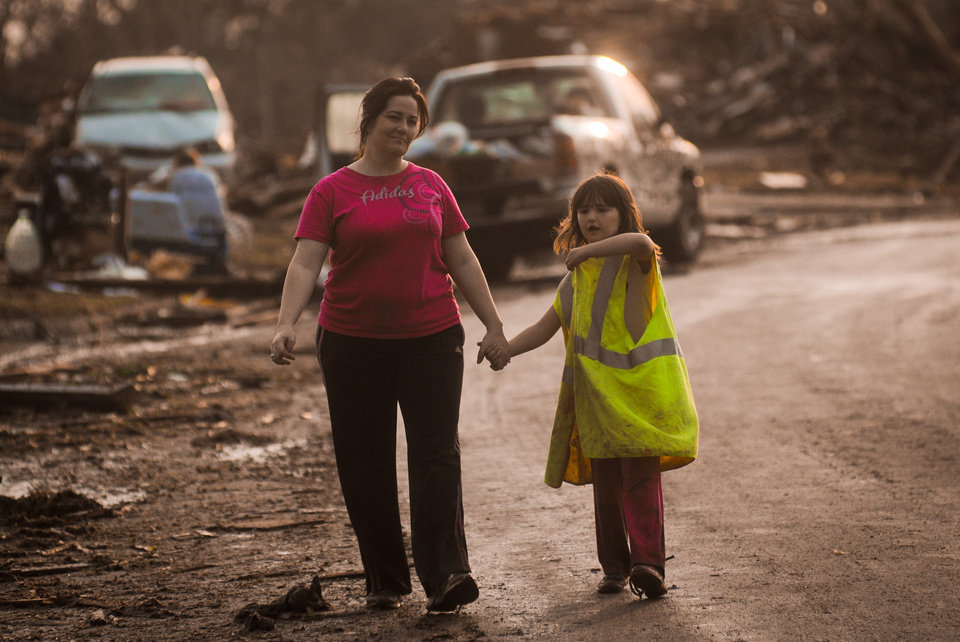 Photo - Summer Roberts and her daughter Addyson Roberts, 7, hold hands after being reuinted after the tornado struck their home on May 20, 2013. Photo by KT King, The Oklahoman