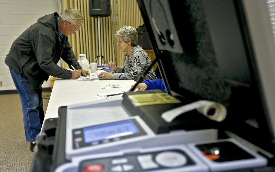 Photo - Volunteer Cindy Ward checks in Carlos Fox to vote at the First Baptist Church on Tuesday Jan. 8, 2013, in El Reno, Okla. for a school bond issue that could lead to the purchase of land and demolition of the church. The new acquisition would be used to build a new math and science wing for the high school. The church is in the process of relocating closer to I-40 in El Reno.  Photo by Chris Landsberger, The Oklahoman