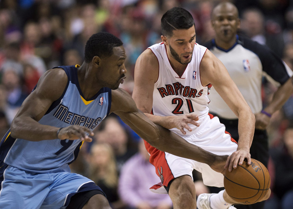 Photo - Toronto Raptors guard Greivis Vasquez (21) battles for the loose ball against Memphis Grizzlies guard Tony Allen, left, during first half NBA basketball action in Toronto on Friday, March. 14, 2014. (AP Photo/The Canadian Press, Nathan Denette)
