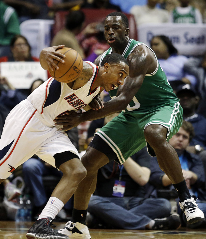 Photo - Atlanta Hawks' Jeff Teague, left, dribbles against Boston Celtics' Brandon Bass in the third quarter of an NBA basketball game, Wednesday, April 9, 2014, in Atlanta. The Hawks won 105-97. (AP Photo/David Goldman)