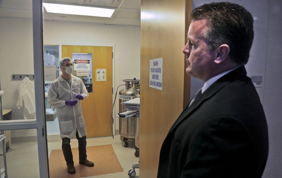 Photo - In this April 15, 2014 photo, Mark Desire, right, assistant director for forensic biology at the Office of Chief Medical Examiner, talks with forensic criminalist Michael Mosco as he prepares to enter the bone grinding room at the Office of Chief Medical Examiner in New York. The room is central to the examination of bone DNA from those who died on Sept. 11, 2001. Forensic scientists are still trying to match the bone with DNA from victims who have never been identified. (AP Photo/Bebeto Matthews)