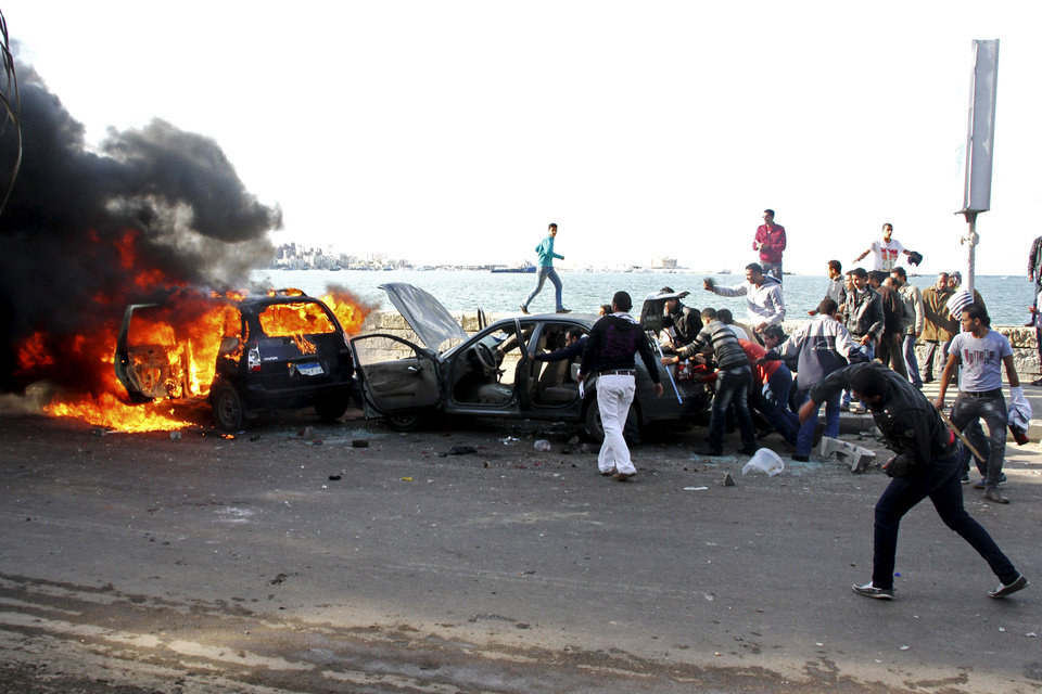 Cars burn during clashes between supporters and opponents of President Mohammed Morsi in Alexandria, Egypt, Friday, Dec. 14, 2012, a day before the referendum on the constitution.  Opposing sides in Egypt's political crisis were staging rival rallies on Friday, the final day before voting starts on a contentious draft constitution that has plunged the country into turmoil and deeply divided the nation.(AP Photo/Ahmed Ramadan) ORG XMIT: CAI111