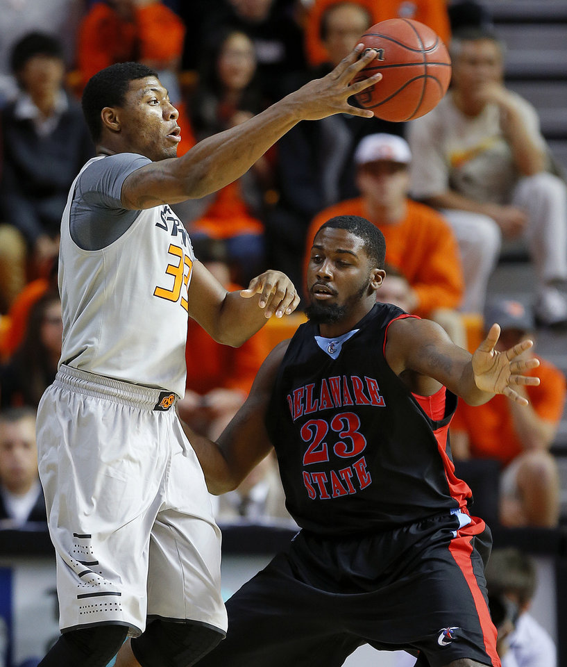Oklahoma State's Marcus Smart (33) passes the ball by Delaware State's Jason Owens (23) during an NCAA college basketball between Oklahoma State University and Delaware State at Gallagher-Iba Arena in Stillwater, Okla., Tuesday, December 17, 2013. Photo by Bryan Terry, The Oklahoman
