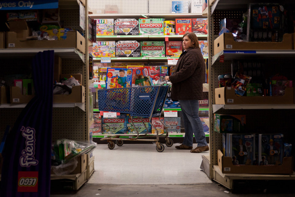 Photo -   A customer examines shelves of toys during Toys